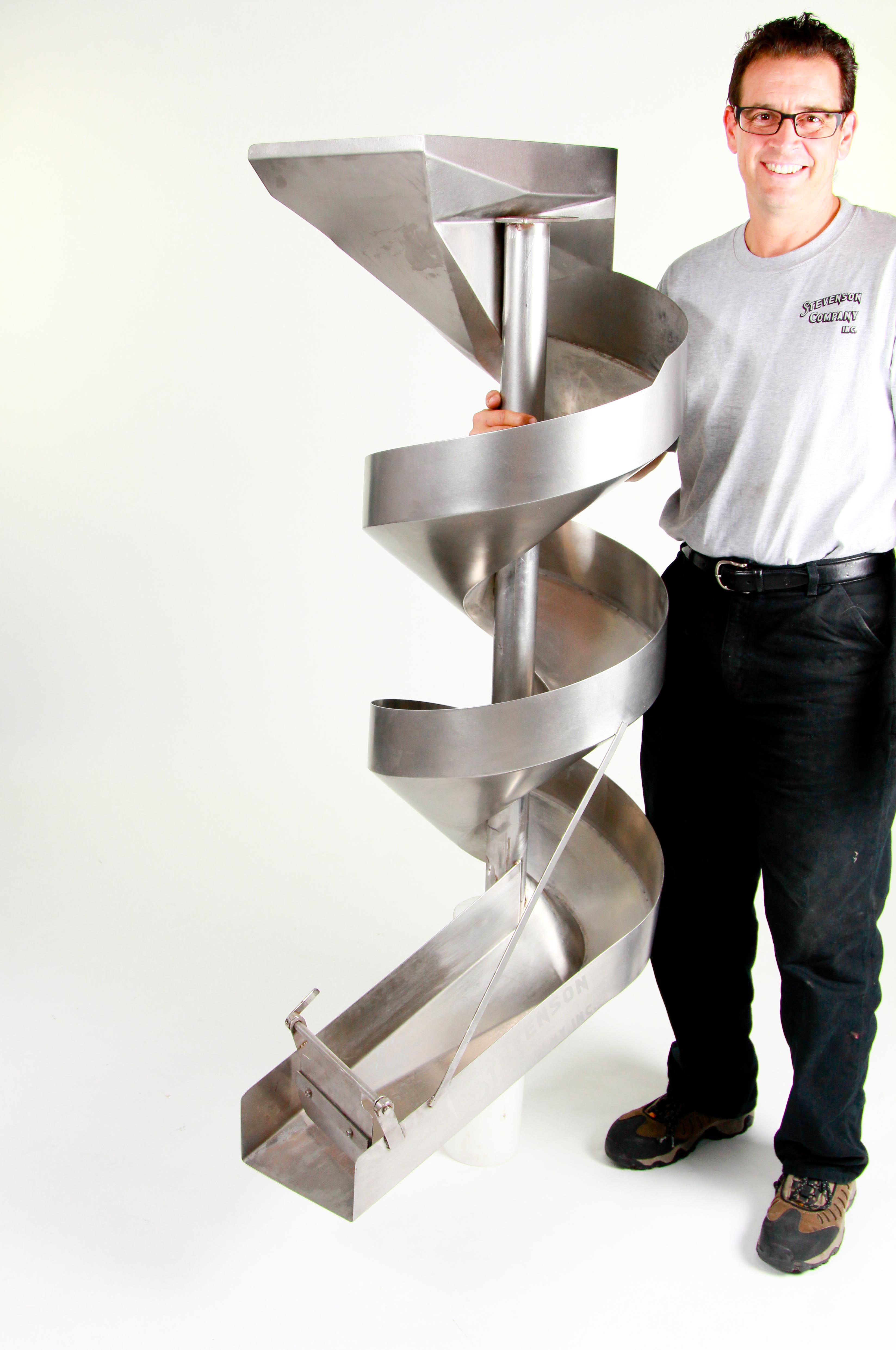 Joe Pennington, President/CEO of Stevenson Company, showing one of their stainless steel spiral chutes